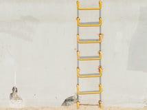 在浅灰色的conrecete墙壁上的黄色梯子 免版税库存图片