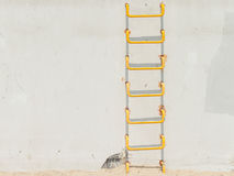 在浅灰色的conrecete墙壁上的黄色梯子 免版税图库摄影
