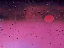 在浅粉红色和黑暗的桃红色背景的许多下落雨 库存照片