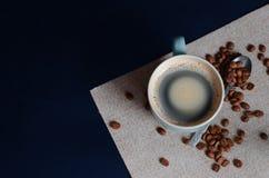 在浅绿色的杯子和整个咖啡豆阿拉伯咖啡的浓哥伦比亚的咖啡 顶视图 免版税库存照片