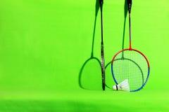 在浅绿色的背景的羽毛球拍和shuttlecock羽毛与文本空间 免版税库存图片