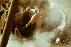 在浅草,东京,日本供以人员祈祷与烧在著名佛教寺庙Senso籍的香火 免版税库存图片