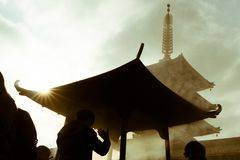 在浅草,东京,日本供以人员祈祷与烧在著名佛教寺庙Senso籍的香火 图库摄影