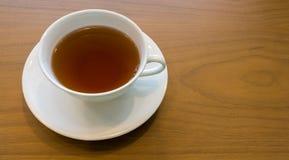 在浅褐色的木纹理的特写镜头白色茶杯 库存图片