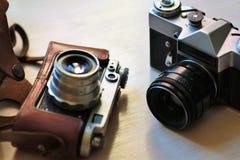 在浅褐色的桌上的两台守旧派葡萄酒照片照相机 一在棕色减速火箭的皮革案件持有人 免版税图库摄影