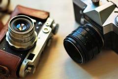在浅褐色的桌上的两台守旧派葡萄酒照片照相机 一在棕色减速火箭的皮革案件持有人 库存照片