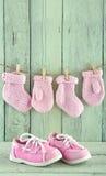 在浅绿色的背景的桃红色小孩鞋子 免版税库存照片