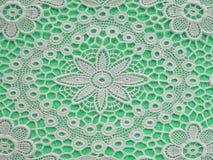 在浅绿色的背景的白色doilie 免版税库存图片