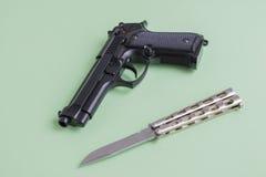在浅绿色的背景的黑手枪和铁刀子 库存图片