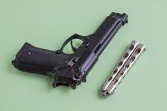 在浅绿色的背景的黑手枪和铁刀子 图库摄影
