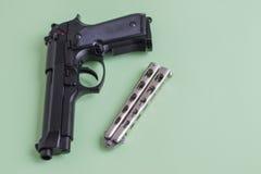 在浅绿色的背景的黑手枪和铁刀子 免版税库存图片