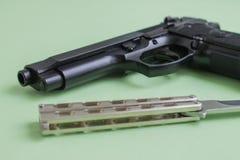 在浅绿色的背景的黑手枪和铁刀子 免版税图库摄影