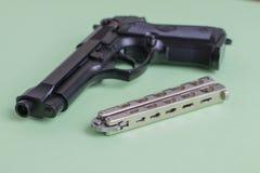 在浅绿色的背景的黑手枪和铁刀子 库存照片