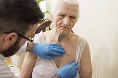 在测试期间的医生老年医学专家 库存图片