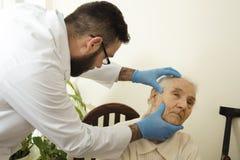 在测试医生期间的医生老年医学专家审查在一个老妇人的皮肤的上变化 免版税库存照片