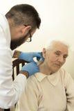 在测试医生期间的医生老年医学专家审查在一个老妇人的皮肤的上变化 库存照片