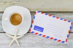 在浓咖啡咖啡的海星在空白的经典航空邮件envel旁边 免版税图库摄影