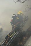 在浓烟吞噬的消防队员 库存图片