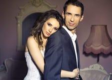 在浪漫姿势的严肃的婚礼夫妇 免版税库存照片
