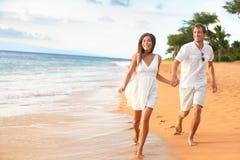 在浪漫旅行蜜月乐趣的海滩夫妇 免版税图库摄影