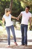 在浪漫步行的年轻夫妇在乡下 图库摄影