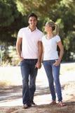 在浪漫步行的年轻夫妇在乡下 免版税库存照片