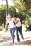 在浪漫步行的年轻夫妇在乡下 免版税图库摄影