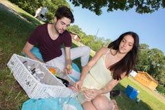 在浪漫野餐期间的画象年轻夫妇在乡下 库存图片