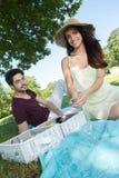 在浪漫野餐期间的画象年轻夫妇在乡下 免版税库存照片