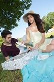 在浪漫野餐期间的画象年轻夫妇在乡下 图库摄影