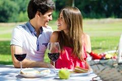 在浪漫野餐的有吸引力的夫妇在乡下 库存图片
