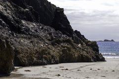在浪潮的蜒蜒岩石峭壁渐近在Kyance小海湾在康沃尔郡 免版税库存图片