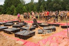 在浮动平台间跑的竞争者在极端障碍桩种族 库存图片