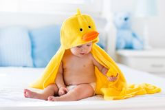 在浴以后的逗人喜爱的婴孩在黄色鸭子毛巾 图库摄影