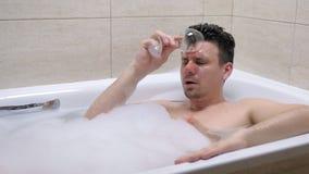 在浴和溢出酒的醉酒的人谎言在他的面孔 股票视频