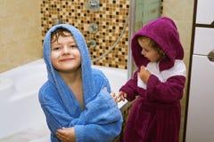 在浴巾的逗人喜爱的孩子在卫生间里 免版税库存照片