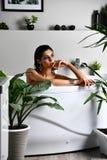 在浴缸和洗浴的年轻美丽的妇女 免版税库存照片