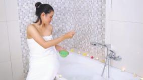 在浴缸的俏丽的妇女播种温泉盐 影视素材