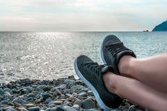 在海、假期和旅行概念年轻女孩休息的说谎在海,在运动鞋特写镜头,夏天冒险的腿的假日, 库存图片