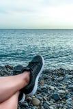 在海、假期和旅行概念年轻女孩休息的说谎在海,在运动鞋特写镜头,夏天冒险的腿的假日, 库存照片