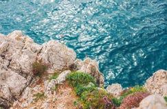在海、夏天海背景、许多飞溅的波浪和石头,晴天上的高峭壁 免版税库存图片