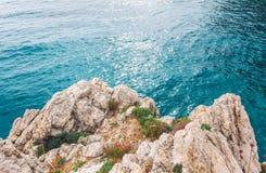 在海、夏天海背景、许多飞溅的波浪和石头,晴天上的高峭壁 库存图片