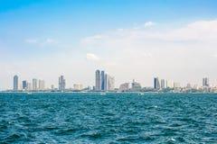 在海、天空和云彩附近加速小船和城市大厦 库存图片