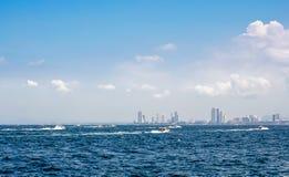 在海、天空和云彩附近加速小船和城市大厦 库存照片