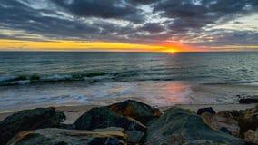 在海上的日落一个多岩石的海滩的 免版税库存照片