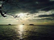 在海上的银色日落,通过云彩晒黑发光 免版税库存照片