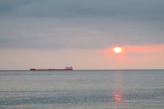 在海上的黄昏红灯,船剪影 免版税库存照片
