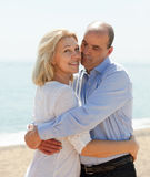 在海假期微笑和拥抱的愉快的夫妇 库存图片