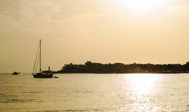 在海和城市的日落 免版税图库摄影