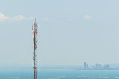 在海和天空背景的电信塔 免版税库存照片